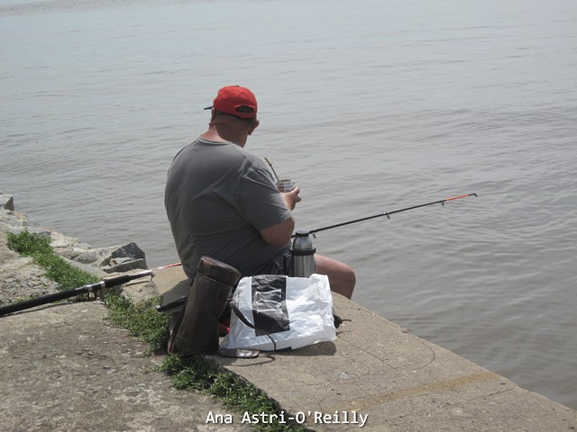 A local fishing from a pier and drinking mate
